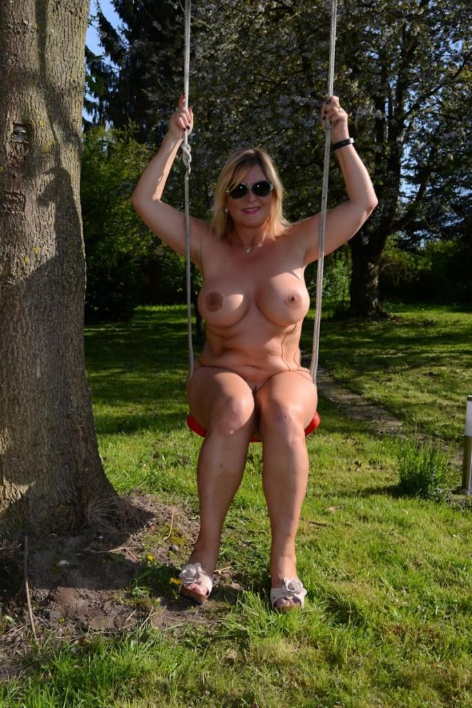 Beautiful woman swinging on a swing outdoors stock photo